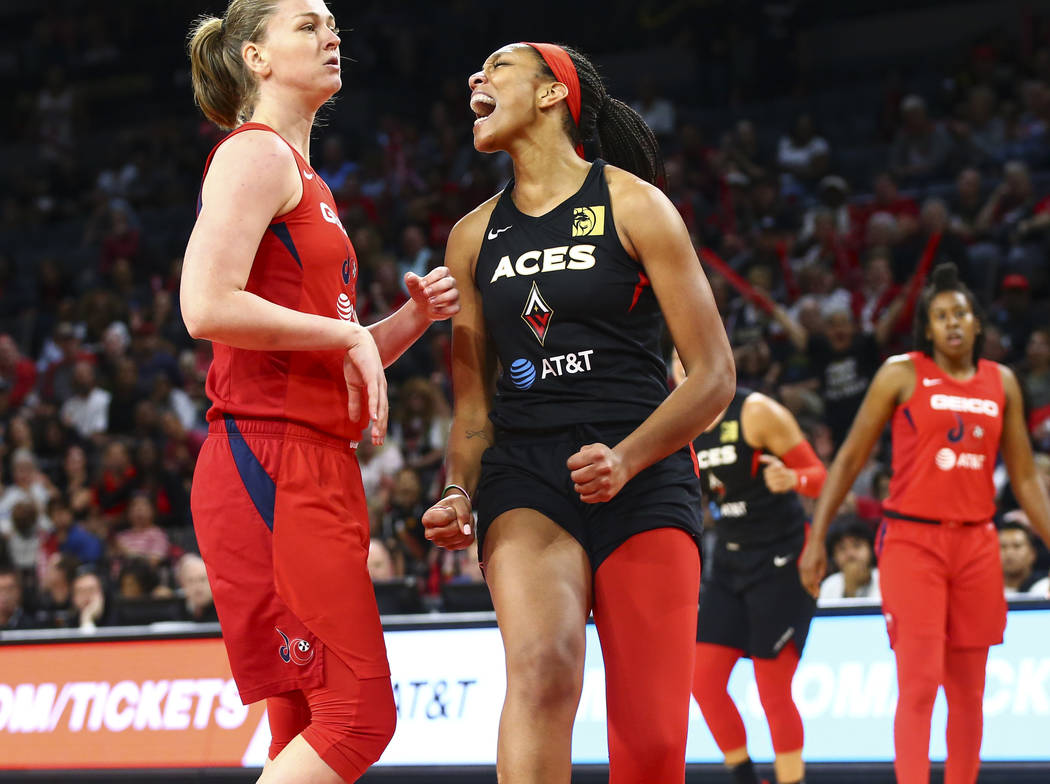 Las Vegas Aces' center A'ja Wilson, right, reacts after drawing a foul in front of Washington M ...