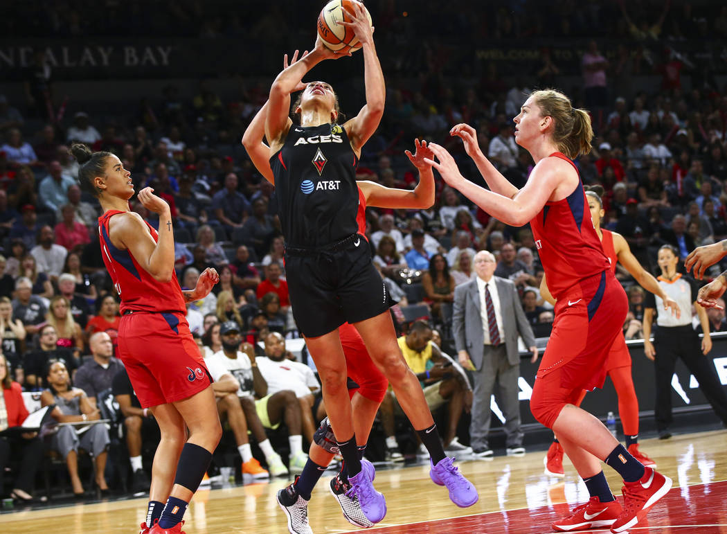 Las Vegas Aces' forward Dearica Hamby, center, looks to shoot under pressure from Washington My ...