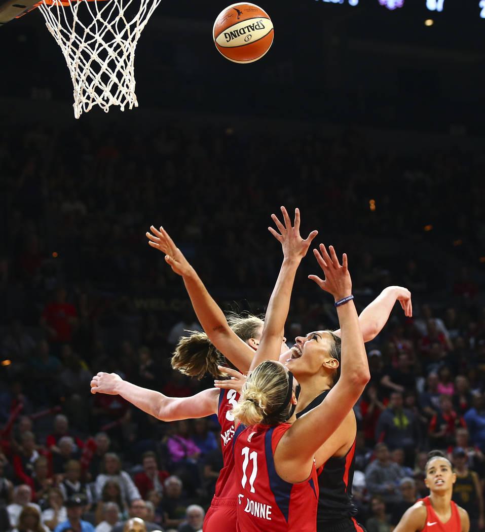 Las Vegas Aces' Liz Cambage, right, shoots between Washington Mystics' Elena Delle Donne (11) a ...