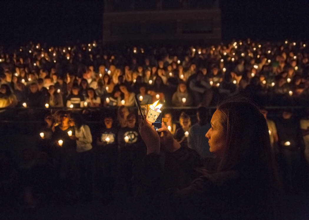 Junior Catriona Palmer, right, takes a photo of attendees during a vigil for four Centennial Hi ...