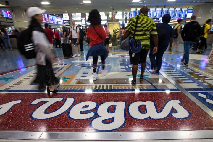 Passengers walk around the baggage claim area at McCarran International Airport ahead of the La ...