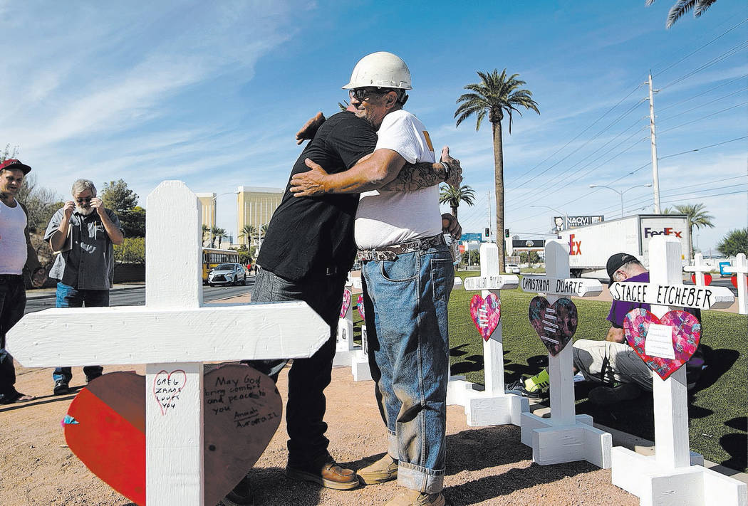 In this Sept. 28, 2018, file photo, cross maker Greg Zanis, right, gets a hug from Mike Warino, ...