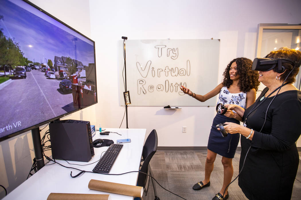 Ebonique Diaz with Terbine helps demonstrate a Google Earth virtual reality system to Lynn Smit ...
