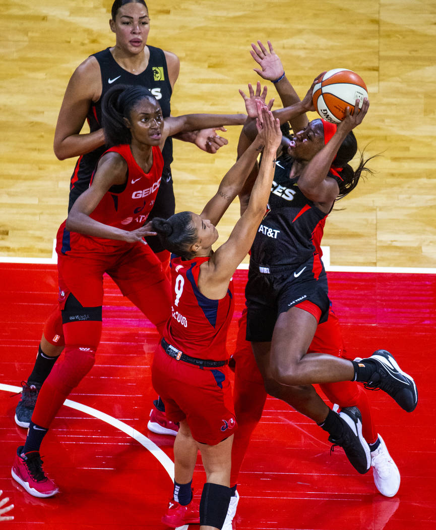 Las Vegas Aces guard Jackie Young (0, right) elevates for a shot attempt over Washington Mystic ...