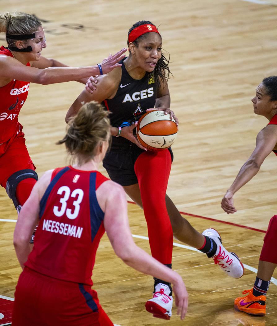 Las Vegas Aces center A'ja Wilson (22, center) attempts to drive through the Washington Mystics ...