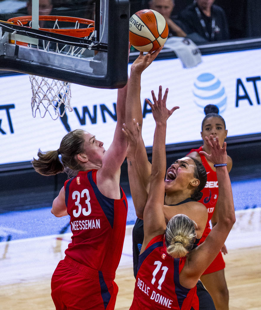 Las Vegas Aces center Liz Cambage (8, right) goes up for a shot attempt under tight defense by ...