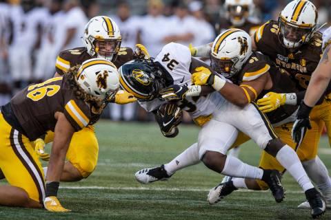 Wyoming defenders Cassh Maulia (46), Logan Wilson (30)and Mario Mora (97) tackle Missouri runni ...