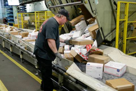 In this Thursday, Dec. 14, 2017 file photos, Steve Robino arranges packages on a conveyor belt ...