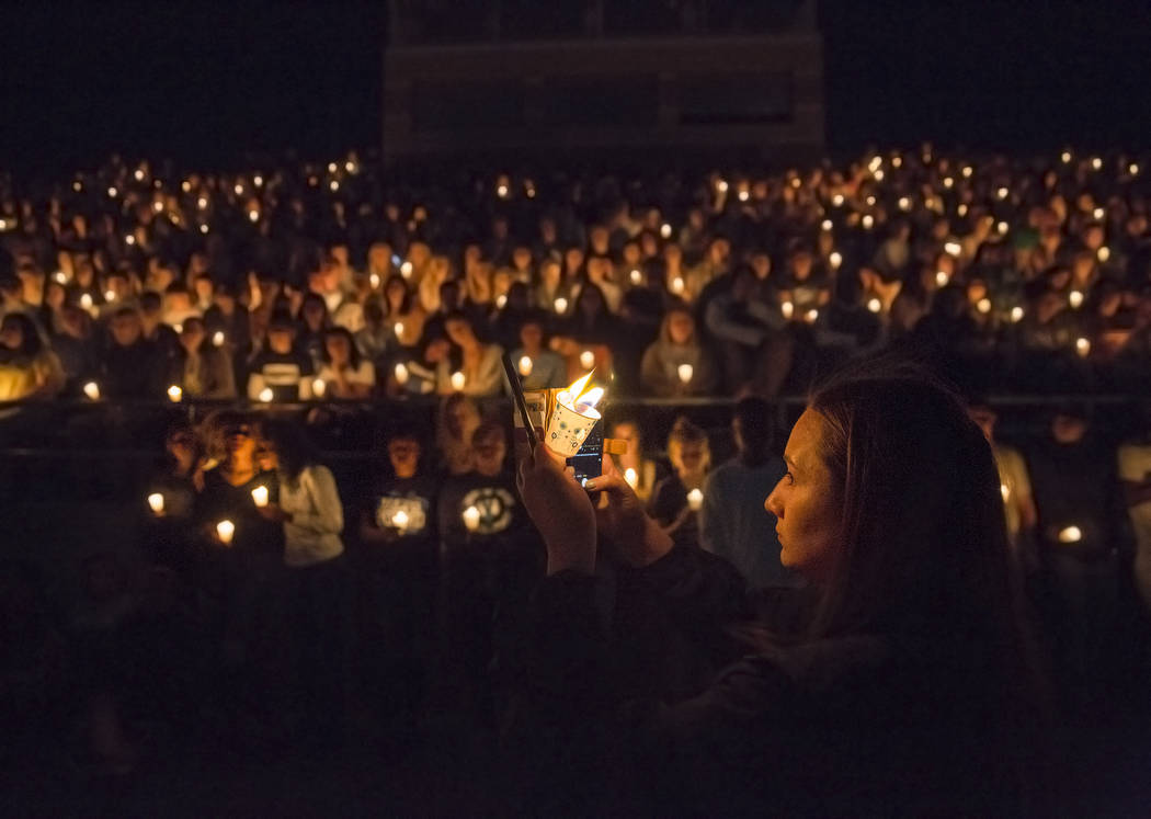 Junior Catriona Palmer, right, takes a photo of attendees during a vigil on April 3, 2018, at C ...