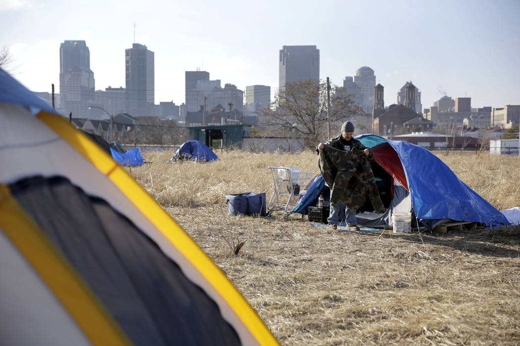 In a Tuesday, Jan. 27, 2015, file photo, Terry, cleans out his tent at a large homeless encampm ...