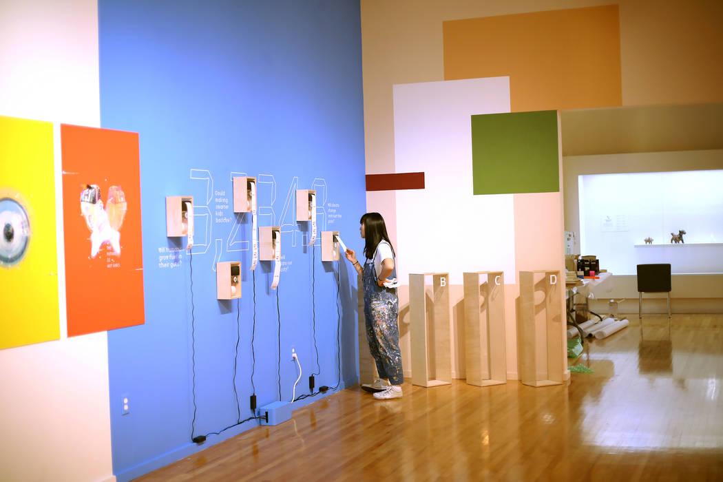 """Artist Amanda Phingbodhipakkiya checks the printing function of her installation """"Strange ..."""