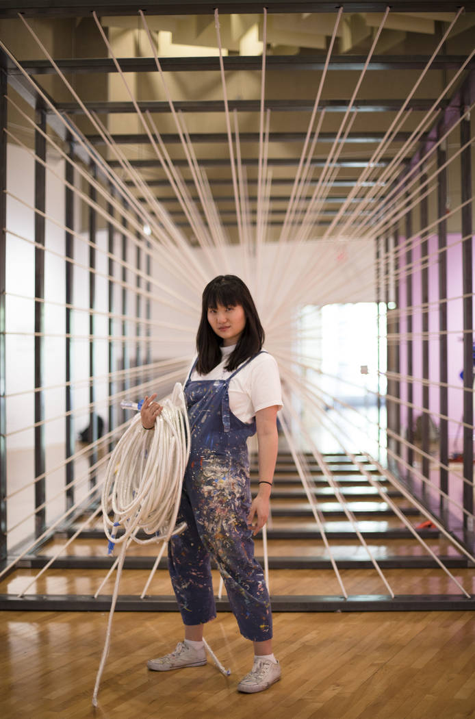 Amanda Phingbodhipakkiya, a neuroscientist-turned-artist, stands in front of one of her install ...