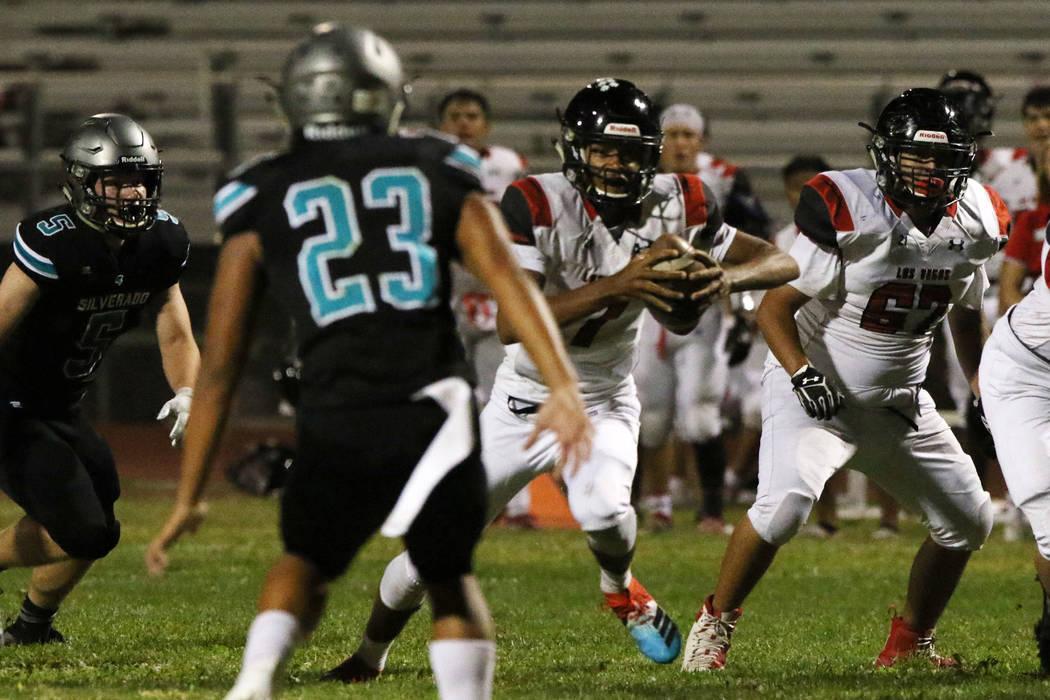 Las Vegas High's quarterback Ja'shawn Scroggins, second right, runs with the ball during the fi ...