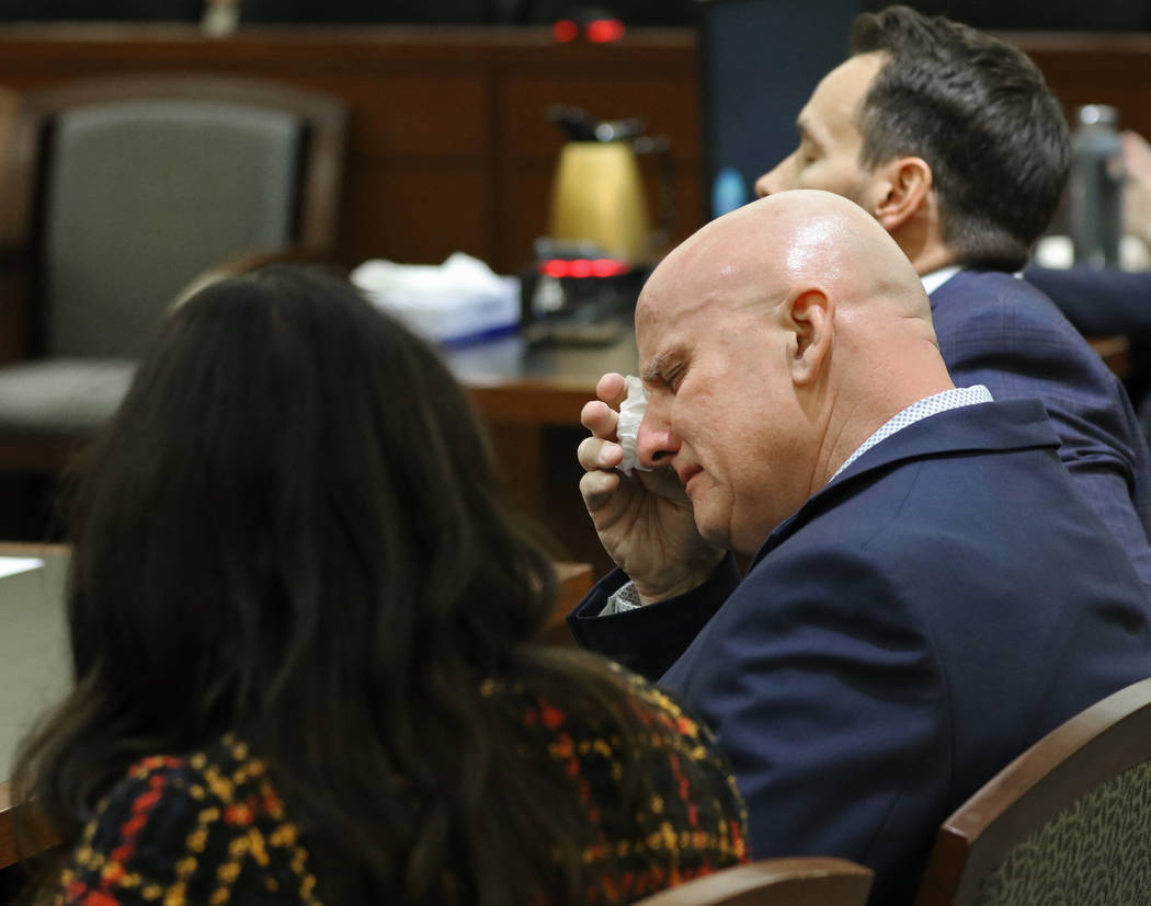 """Las Vegas police Lt. James """"Tom"""" Melton, middle, wipes tears from his eyes after he w ..."""