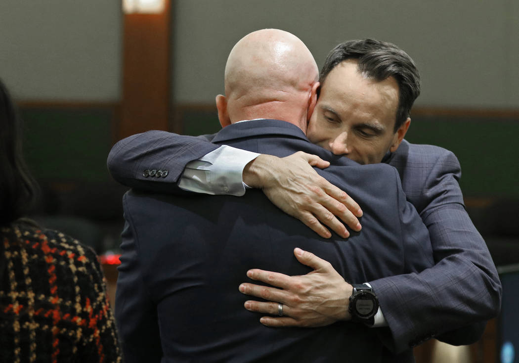 "Defense attorney Josh Tomsheck, facing, hugs Las Vegas police Lt. James ""Tom"" Melton, ..."