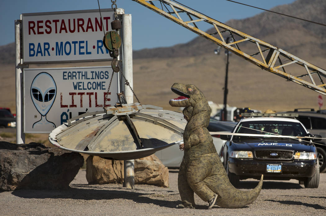 A T-Rex costumed festivalgoer walks over to the flying saucer outside the Little A'Le'Inn durin ...