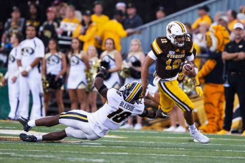 Wyoming quarterback Sean Chambers runs for a touchdown past Missouri defender Joshuah Bledsoe i ...