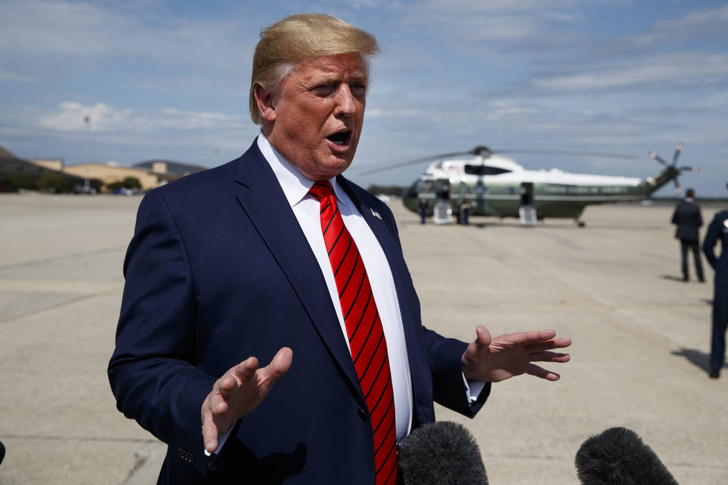 President Donald Trump talks with reporters after arriving at Andrews Air Force Base, Thursday, ...