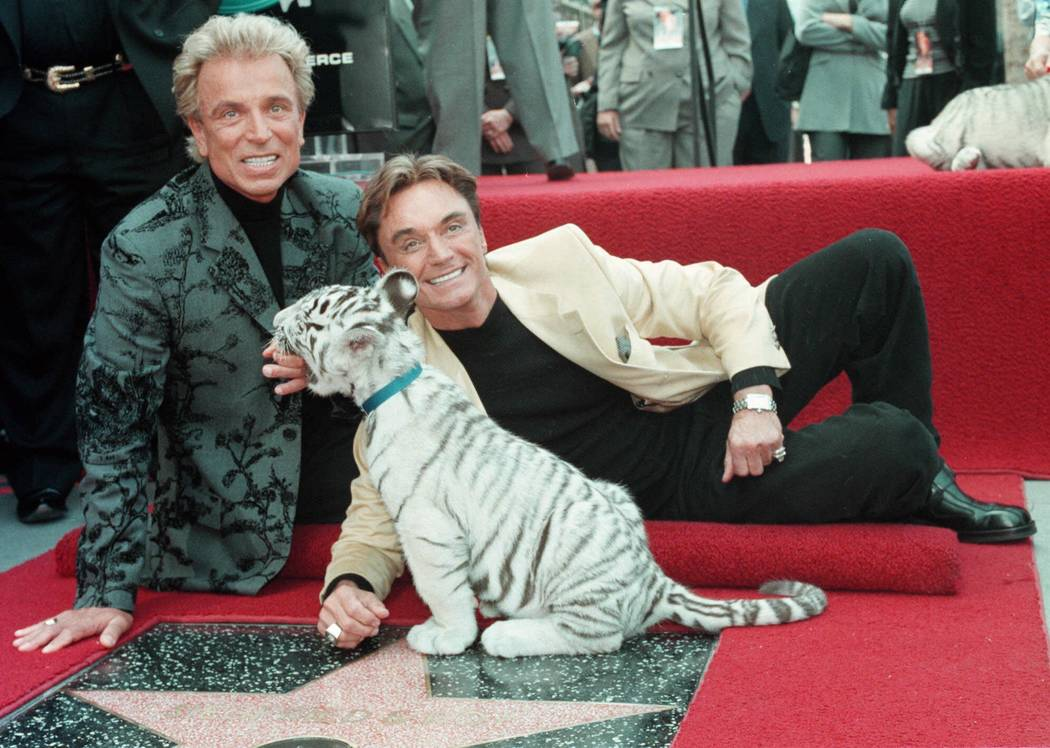Illusionists Siegfried Fischbacher, left and Roy Horn with a white tiger cub after they unveile ...