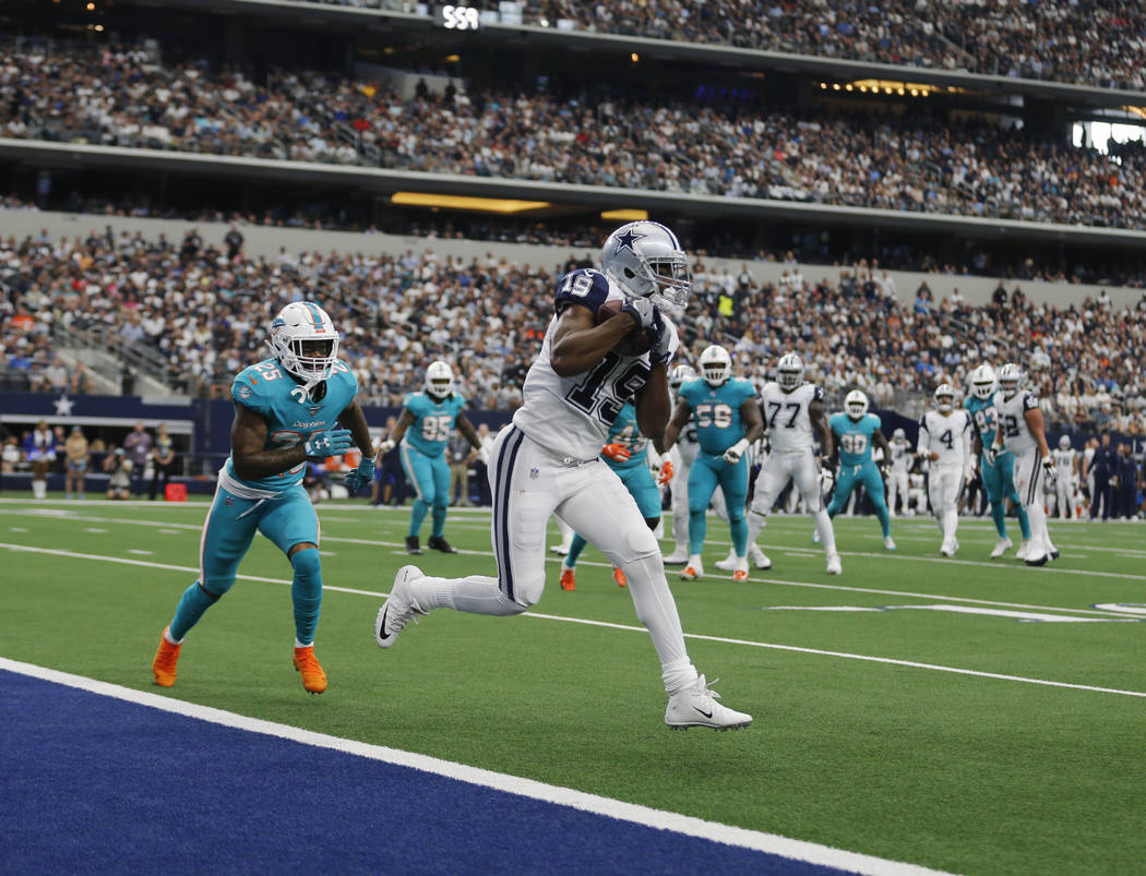 Dallas Cowboys wide receiver Amari Cooper (19) catches a touchdown pass in front of Miami Dolph ...