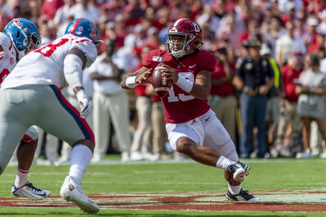 Alabama quarterback Tua Tagovailoa (13) runs looking to throw against Mississippi during the fi ...