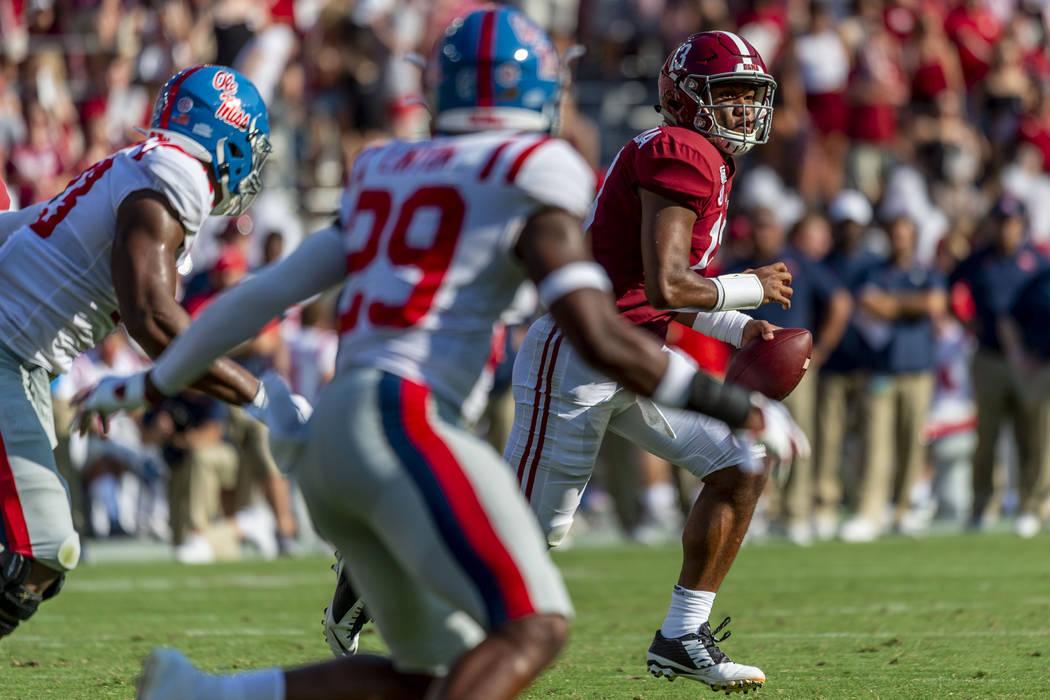 Alabama quarterback Tua Tagovailoa (13) rolls out against Mississippi during the first half of ...