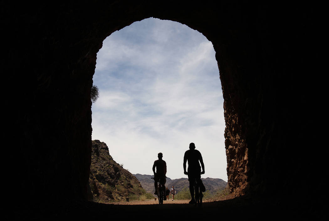Riders bicycle through a tunnel along the Historic Railroad Trail near Lake Mead. (John Locher/ ...