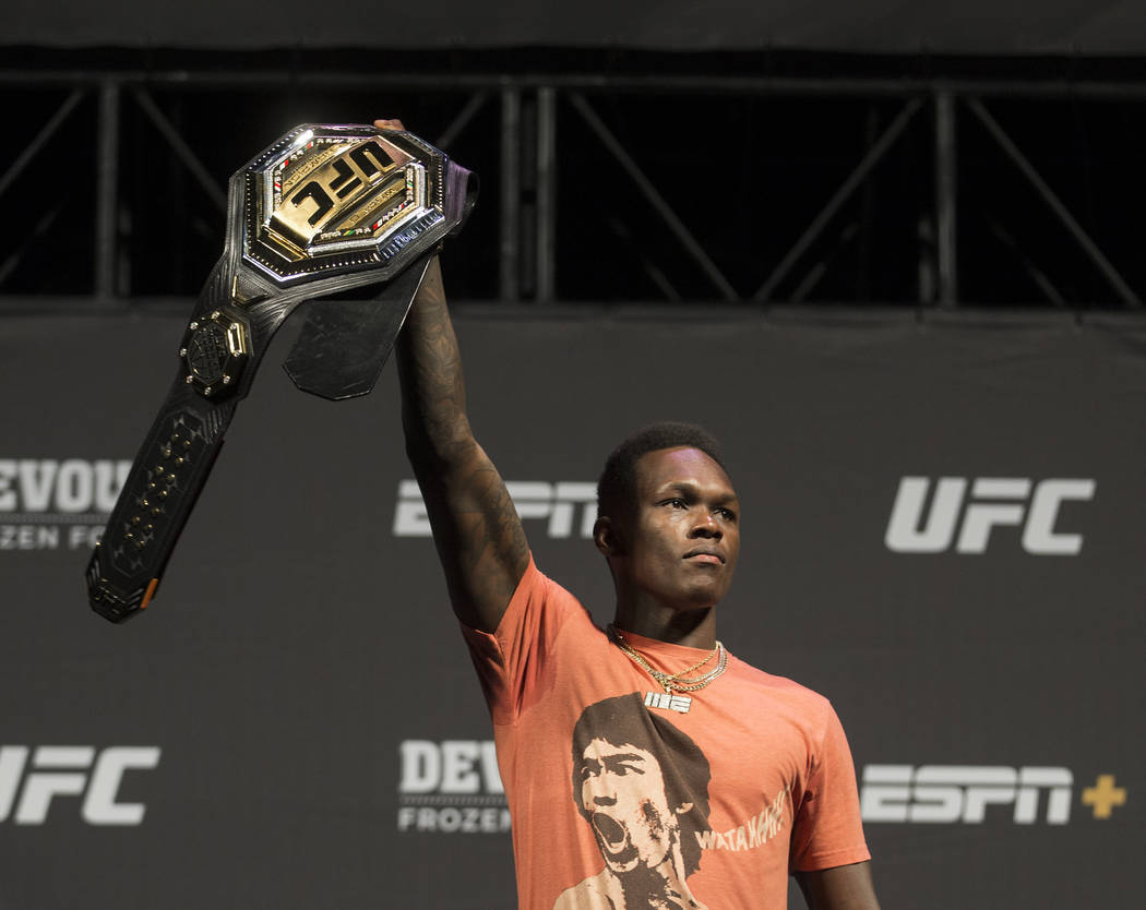 UFC interim middleweight champion Israel Adesanya holds up his belt during a press conference o ...
