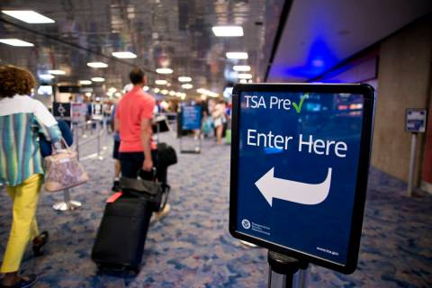 Passengers walk toward the TSA PreCheck security line at McCarran International Airport in Las ...