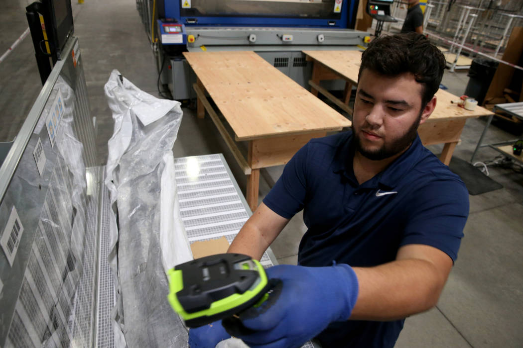 Jose Magdaleno makes a custom box by scanning the dimensions of a car part at the new CarParts. ...