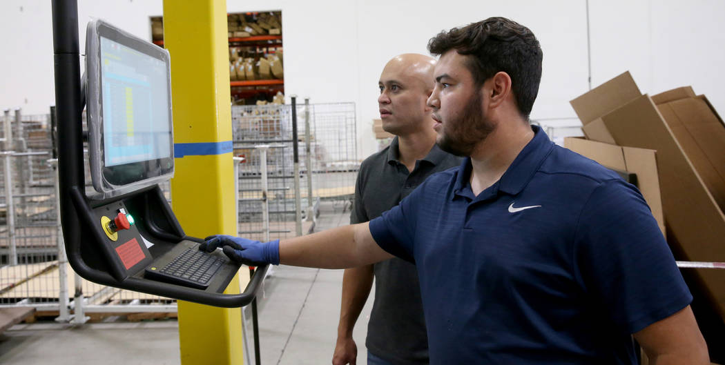 Jose Magdaleno, right, and Joseph Divino make a custom box after scanning the dimensions of a c ...