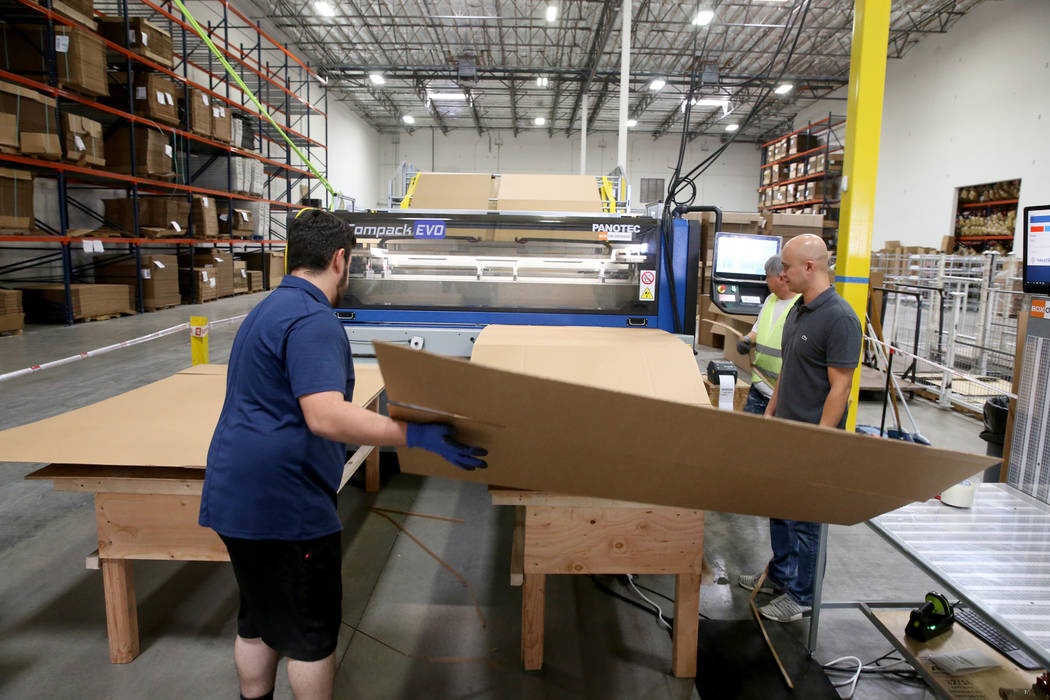 Jose Magdaleno, from left, Marlon Obsuna and Joseph Divino make a custom box after scanning the ...