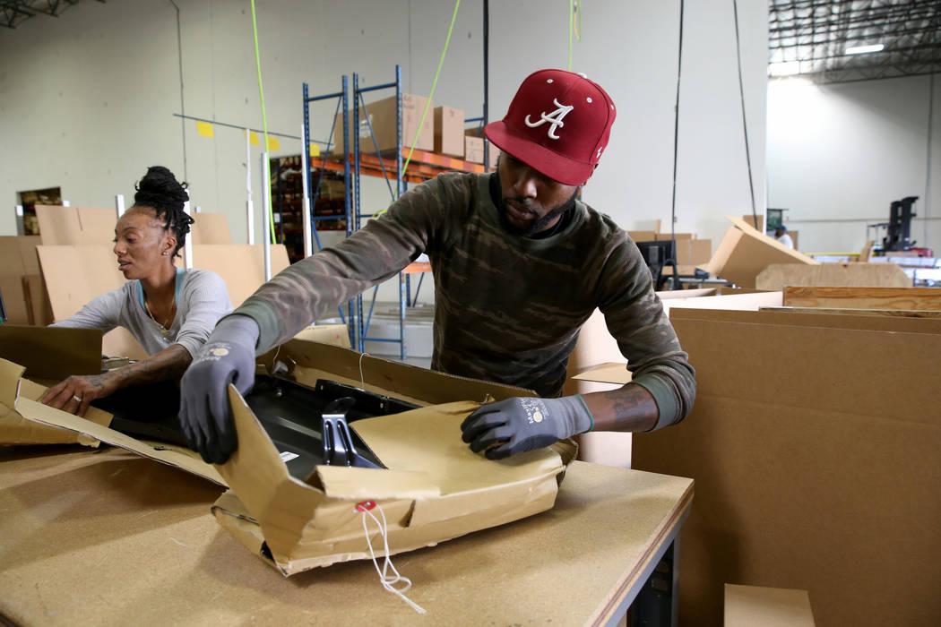 Donald Brown and Brandi Gordon package car parts at the new CarParts.com distribution facility ...