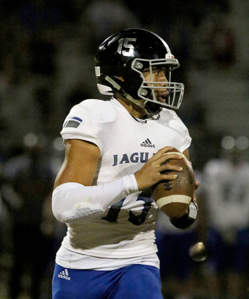 Desert Pines High quarterback Rjay Tagataese (15) looks for an opening as he runs with the ball ...
