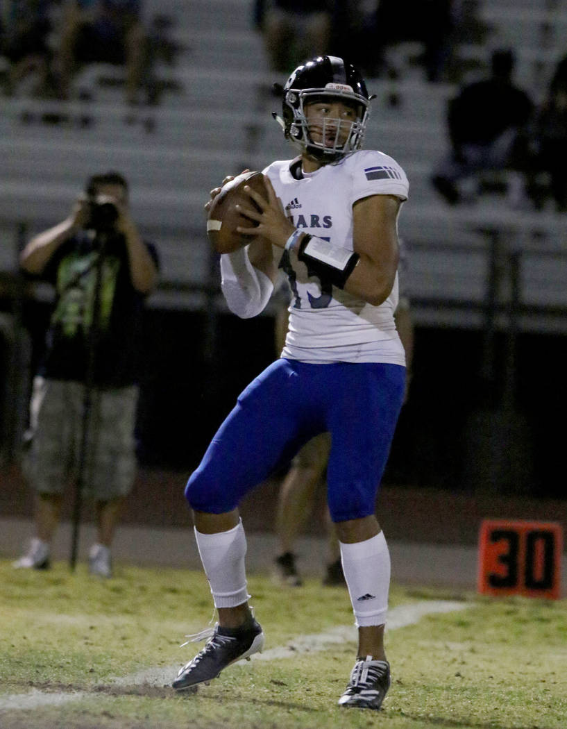 Desert Pines High quarterback Rjay Tagataese (15) looks for an opening as he prepares to throw ...