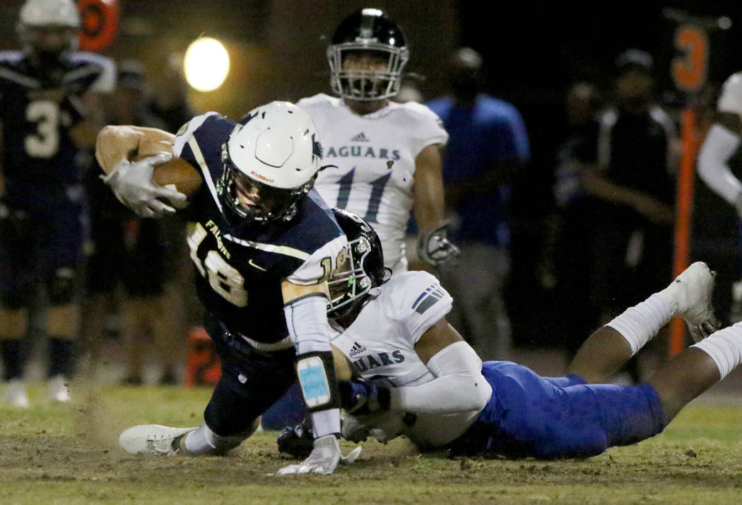 Foothill High's wide receiver Thomas Fisher-Welch (18) is take down by Desert Pines High's Core ...