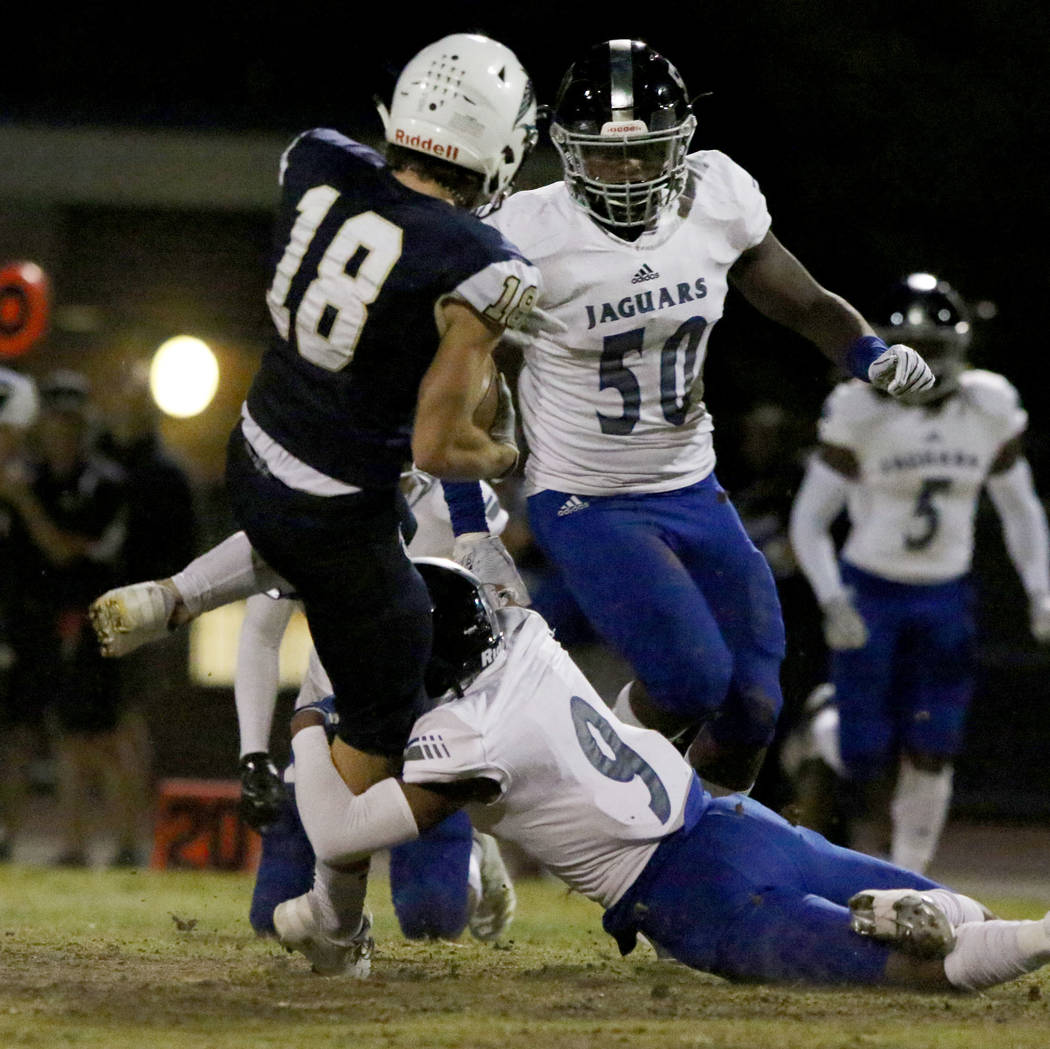 Foothill High's wide receiver Thomas Fisher-Welch (18) is tackled by Desert Pines High's Corey ...