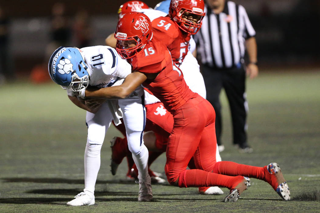 Arbor View's Anthony Jones (15) tackles Centennial's quarterback Colton Tenney (1) during the s ...