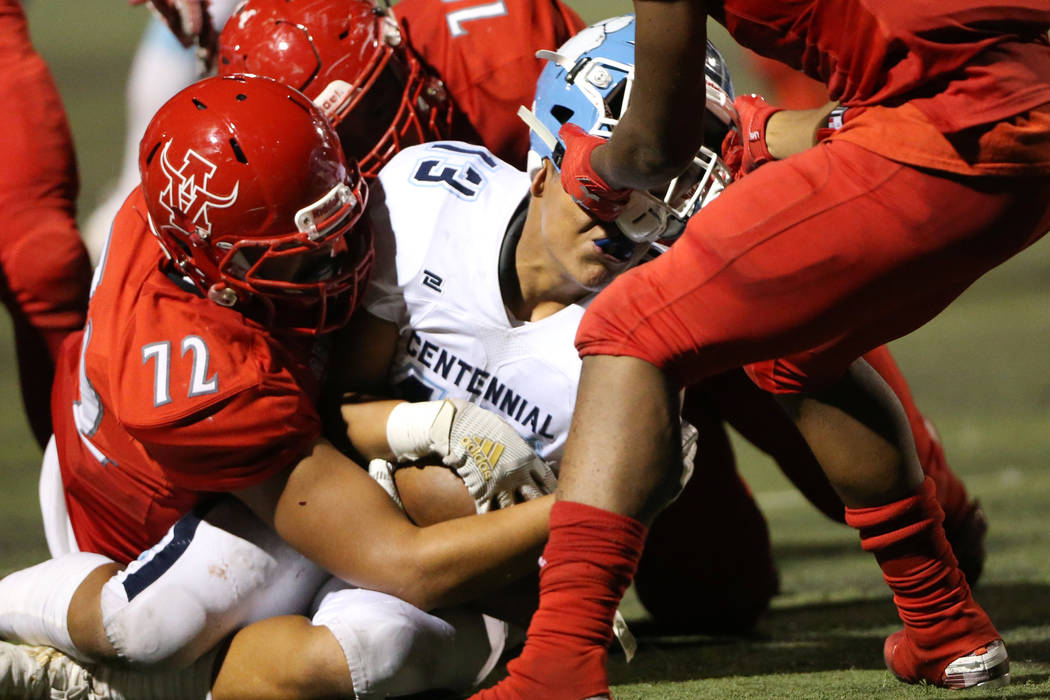 Arbor View's Jaedyn Jackson (11) rips the helmet from Centennial's Ronaven Mokiao (13) for a pe ...