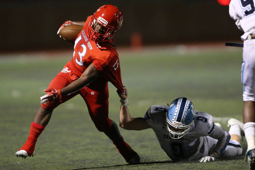 Arbor View's D'Andre Washington (13) deflects a tackle from Centennial's Nate Conger (9) during ...