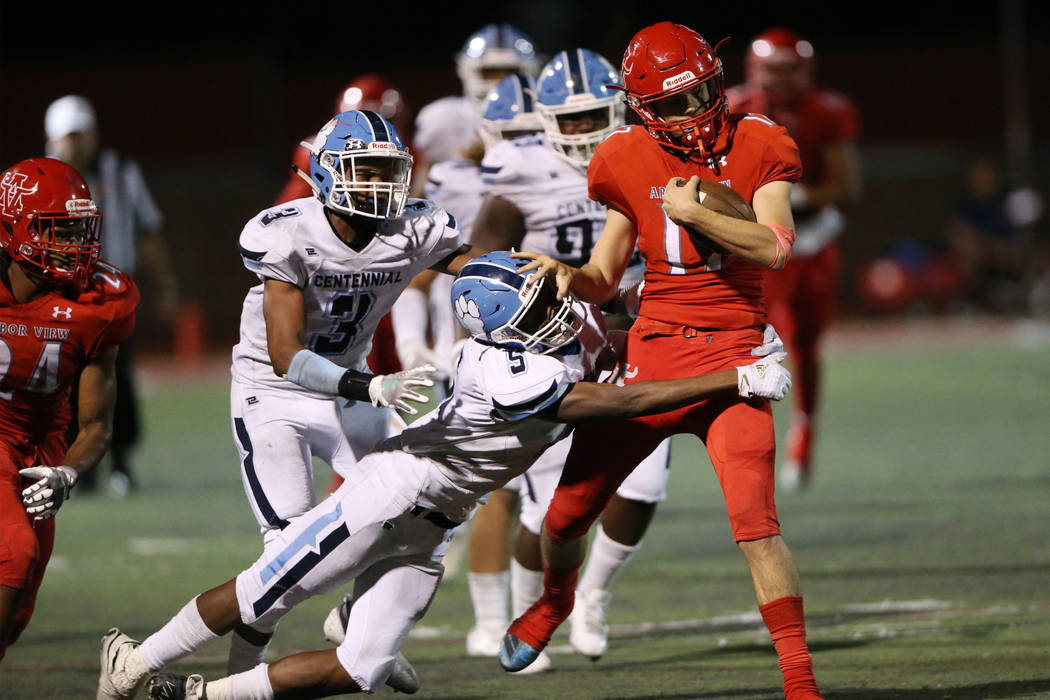 Centennial's Tyrone McCoy (5) with Donte Washington (3) tackles Arbor View's Kyle Holmes (17) d ...
