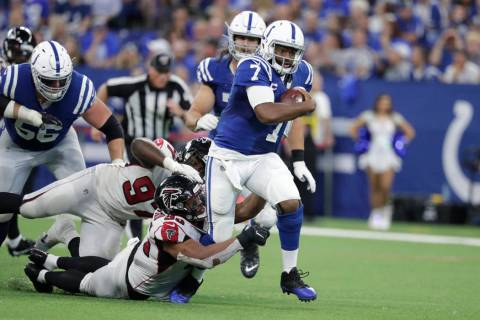 Indianapolis Colts quarterback Jacoby Brissett (7) runs out of the tackle of Atlanta Falcons de ...