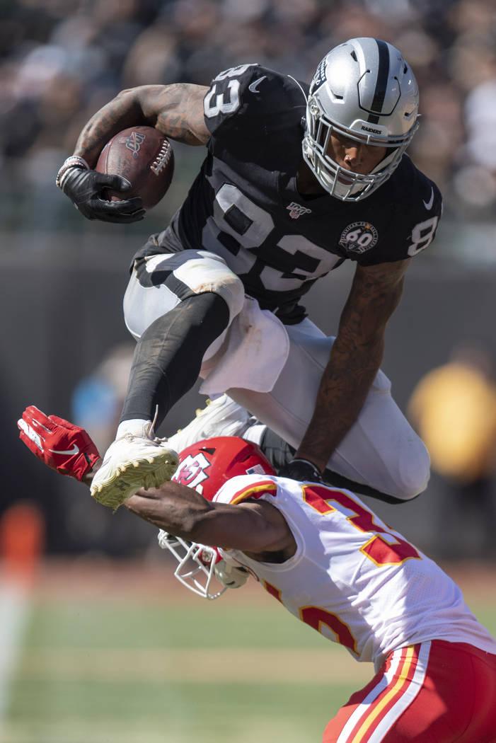 Oakland Raiders tight end Darren Waller, top, leaps over Kansas City Chiefs cornerback Charvari ...
