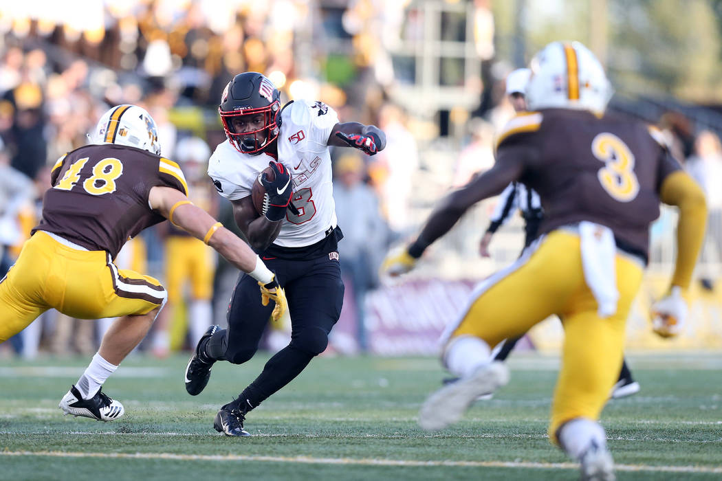 UNLV running back Charles Williams attempts to juke past University of Wyoming linebacker Chad ...