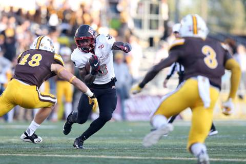 UNLV running back Charles Williams attempts to juke past University of Wyoming linebacker Chad ...