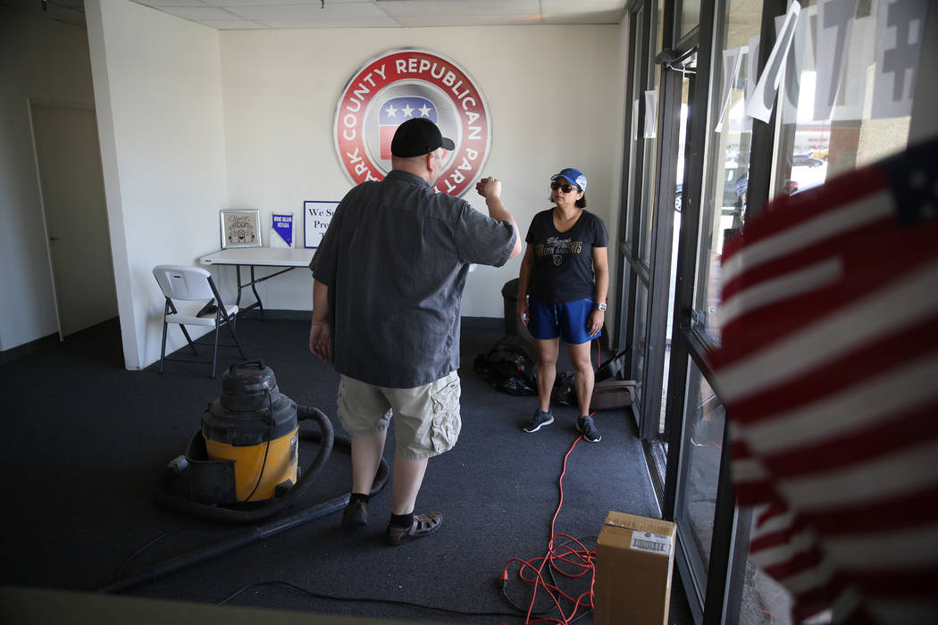 Volunteers Richard MacLean, left, and Diana Gomez, talk inside the Clark County Republican Part ...