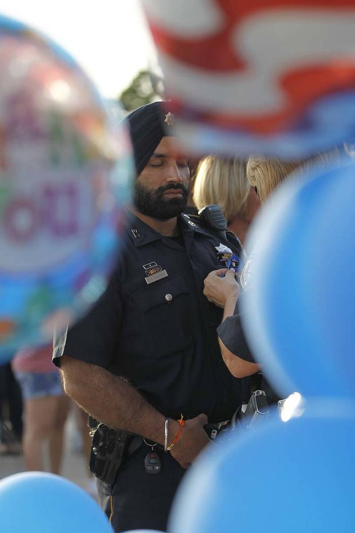 In this Aug. 29, 2015, photo, Harris County Sheriffs deputy Sandeep Dhaliwal gets a blue ribbon ...