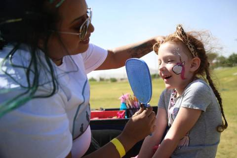 Adelaide Satterwhite, 6, looks at the face painting by Christian Ramos, during a celebration of ...