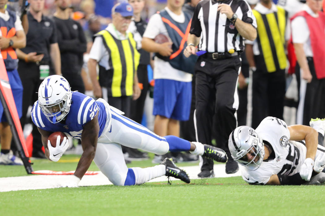 Indianapolis Colts running back Marlon Mack (25) sheds a tackle from Oakland Raiders free safet ...
