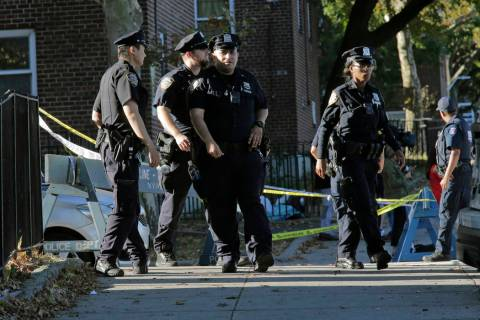 Emergency personnel walk near the scene of a fatal shooting of a New York City police officer i ...